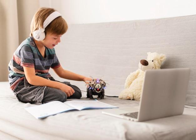 Kind met koptelefoon virtuele lessen bijwonen