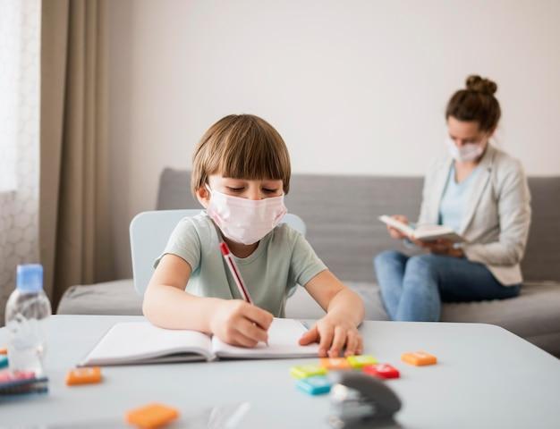 Kind met medisch masker dat thuis wordt begeleid