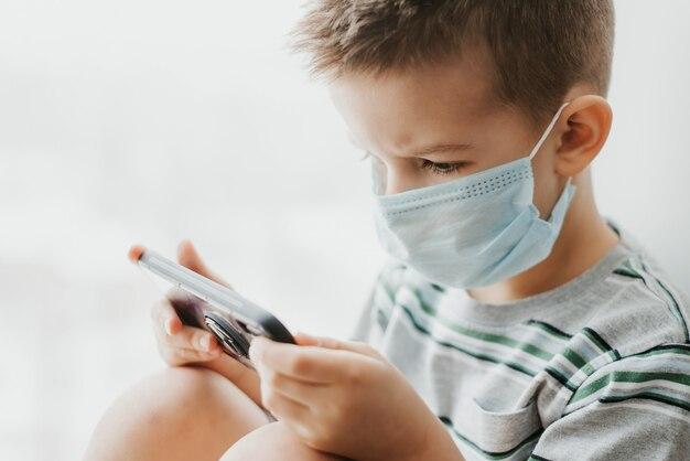 Kind met medisch masker zit in quarantaine en kijkt naar de telefoon tijdens de covid-19