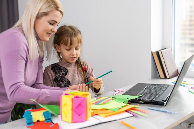 Kind met moeder heeft plezier met het knippen van schaarpapier in de kleuterschool. moeder en dochter maken papierambachten