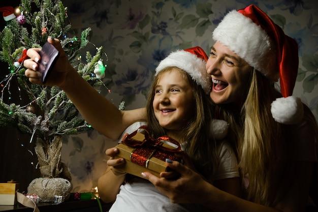 Kind met moeder in kerstmutsen met een videogesprek op eerste kerstdag, zittend op een bank in de woonkamer met kerstboom thuis