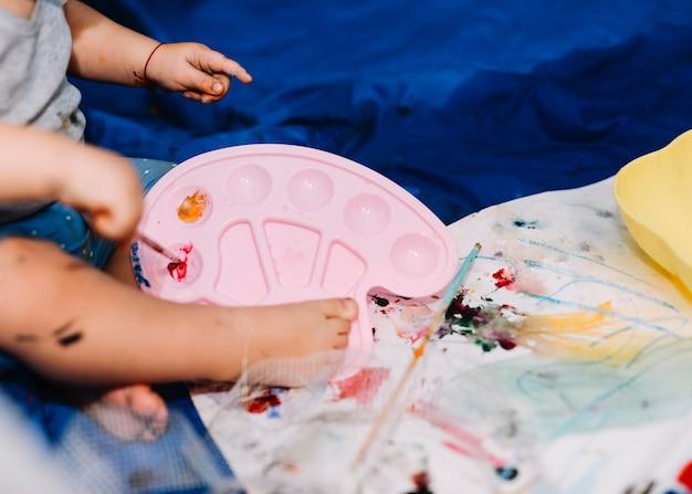 Kind met palet en penseel in de buurt van papier op coverlet