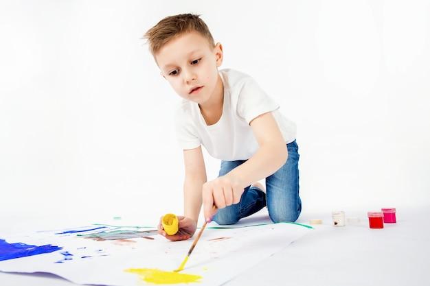 Kind met penseel. 9-jarige jongen, moderne kapsel, wit shirt, spijkerbroek trekt penseel geïsoleerd. studio.