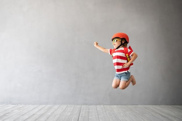 Kind met raket springen tegen grijze betonnen muur.