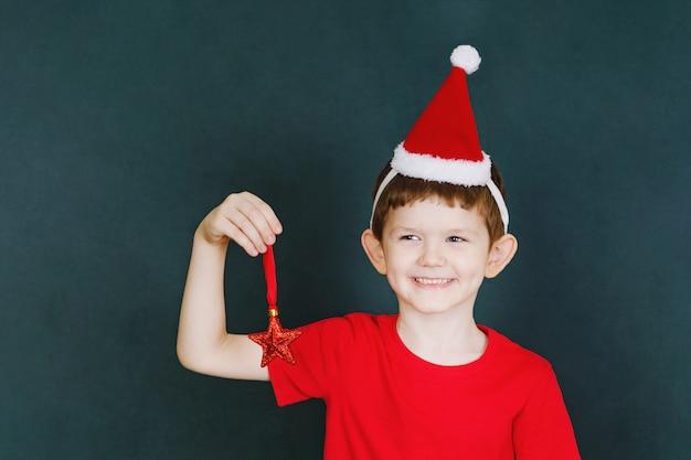 Kind met rode t-shirt en kerstmuts