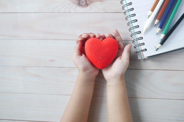Kind met rood hart op tafel