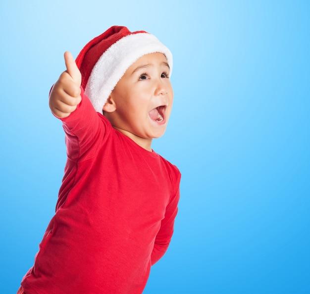 Kind met santa's hoed en duim omhoog