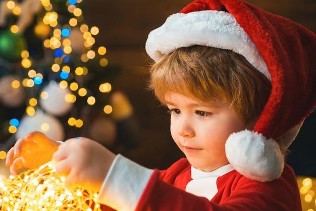 Kind met slingerlichten bij kerstboom en open haard op de vooravond van kerstmis