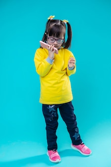 Kind met smartphone. nieuwsgierige kleine dame met het syndroom van down smartphone aan haar wang vastmaken en praten