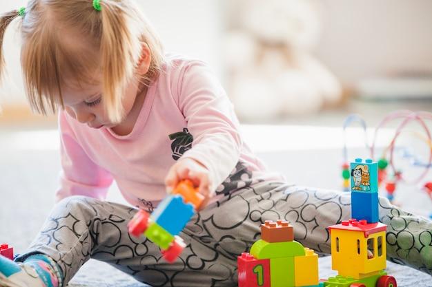 Kind met speelgoed in speelkamer