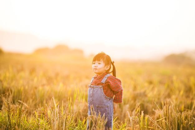Kind met speelgoed vliegtuig in de natuur bij zonsondergang