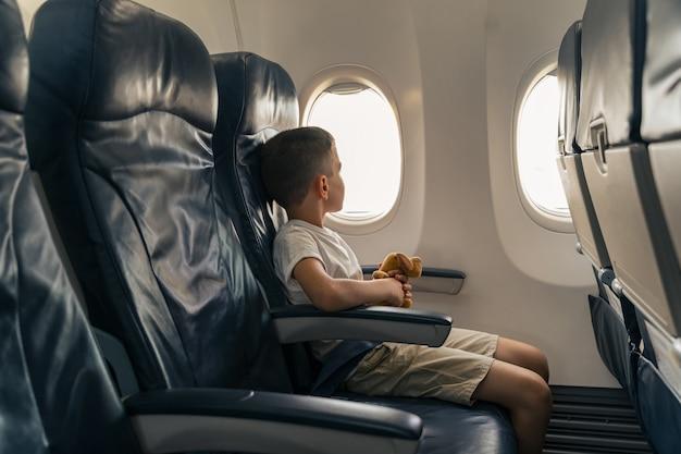 Kind met speelgoed zittend op vliegtuigstoel