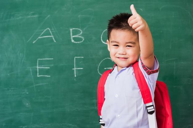 Kind met student uniform en schooltas glimlacht en verschijnt duim