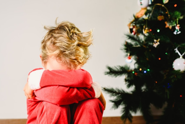 Kind met vermomming, angstig en verdrietig op eerste kerstdag met een boos gezicht naast de kerstboom tijdens het wachten op de kerstman