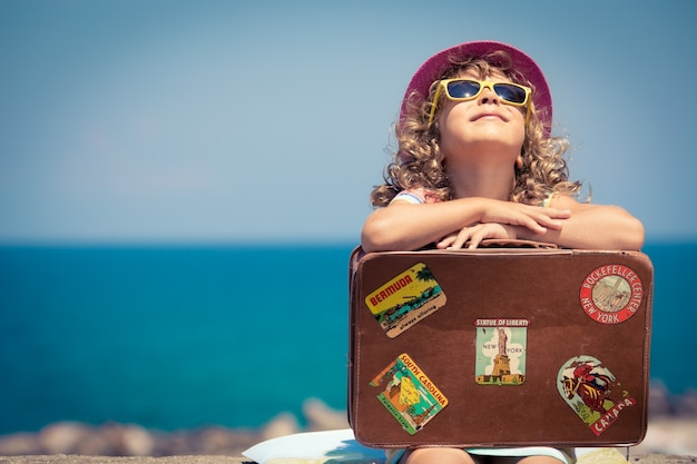 Kind met vintage koffer op zomervakantie. reis- en avontuurconcept