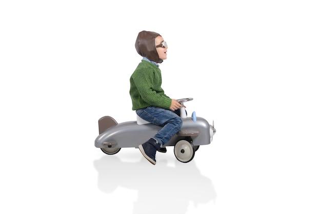 Kind met vliegeniershoed klaar om te vliegen met een speelgoedvliegtuig toy
