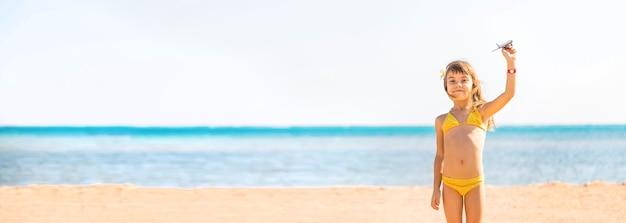 Kind met vliegtuigen in hand op het strand