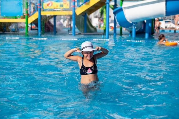 Kind met witte strohoed in waterpark, klein gebruind meisje in zwart zwempak met watermeloenpatroon...