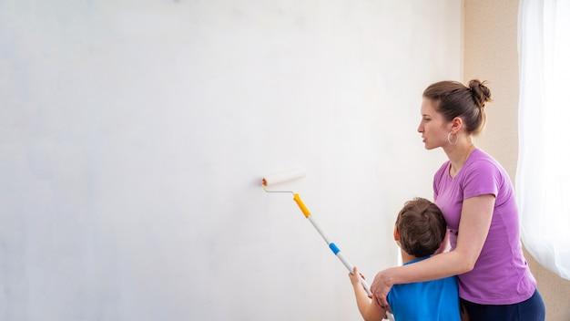 Kind met zijn moeder schildert de muren