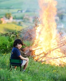 Kind naast het grote vuur
