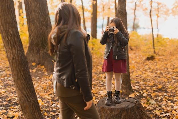 Kind neemt een foto van haar moeder op retro camera in herfstparkhobby's en vrijetijdsconcept
