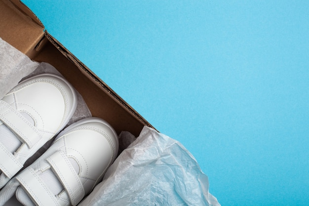 Kind nieuwe witte sportschoenen of sneakers in de schoenendoos op de lichtblauwe pastel achtergrond. nieuwe schoenen uitpakken. kopieer ruimte voor tekst