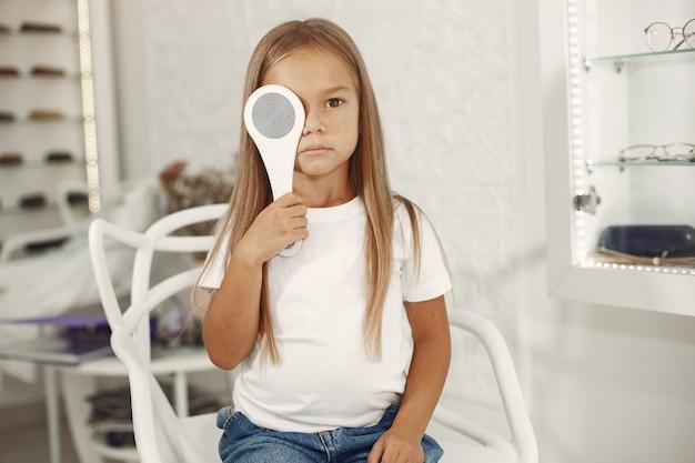 Kind oogtest en oogonderzoek. meisje met oogcontrole, met phoropter. oogtest voor kinderen