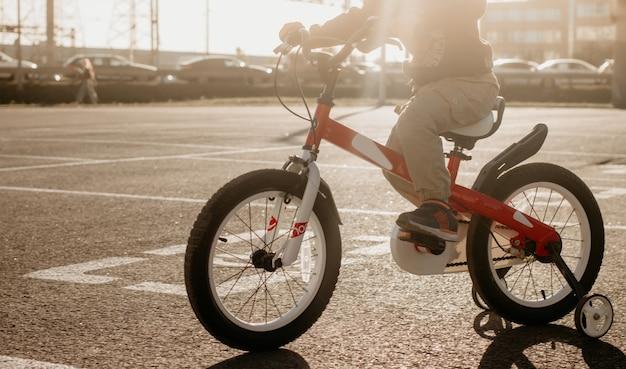 Kind op een fiets op asfaltweg in de vroege ochtend jongen op de fiets in de stad