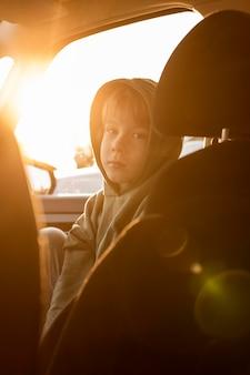 Kind op een roadtrip in de auto met zonnestralen