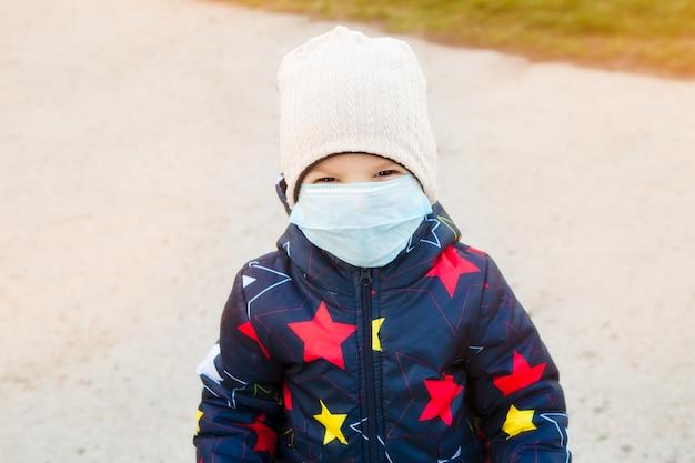 Kind op een wandeling in een stadspark in een medisch masker wandelen op straat tijdens de quarantaineperiode van de coronavirus pandemie in de wereld. veiligheidsmaatregelen en opvoeding van kinderen.