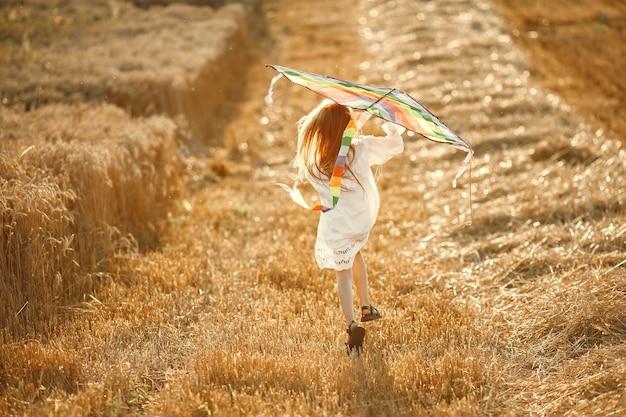 Kind op een zomergebied. klein meisje in een schattige witte jurk. kind met een vlieger.