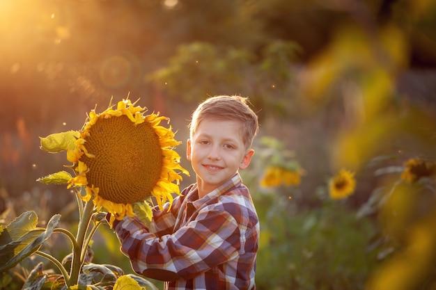 Kind op het gebied van zonnebloem is een kleine boer op zonnige zomerdag. kleine jongen jongen spelen op velden bloemen.