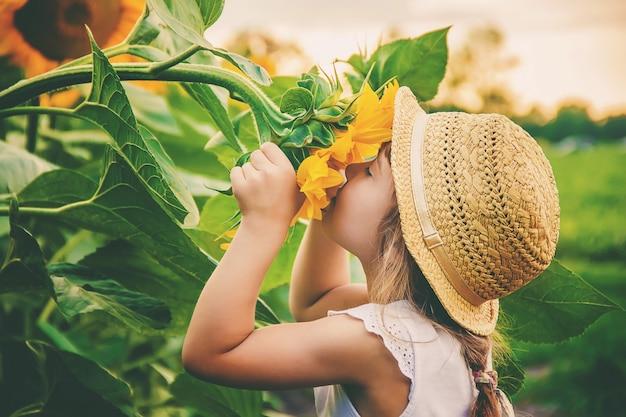 Kind op het gebied van zonnebloemen is een kleine boer. selectieve aandacht.