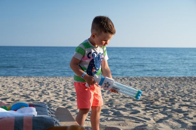 Kind op het strand met een waterpistool.