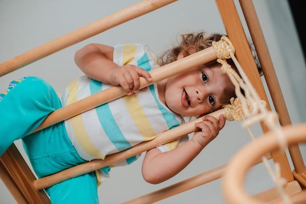 Kind op jonge leeftijd van 1,5 jaar houdt zich bezig met het houten sportcomplex voor kinderen thuis.