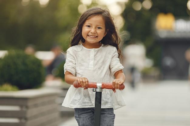 Kind op kickscooter in park. kinderen leren rolschaatsen. klein meisje schaatsen op zonnige zomerdag.