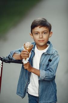 Kind op kickscooter in park. kinderen leren rolschaatsen. kleine jongen schaatsen op zonnige zomerdag.