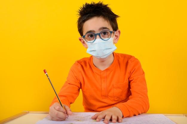 Kind op school met gezichtsmasker voor covid-19 coronavirus op geel