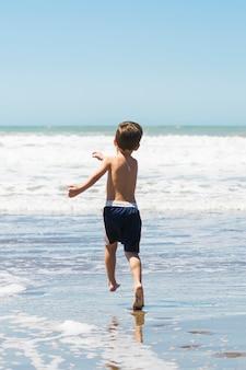 Kind op zeekust die in water loopt