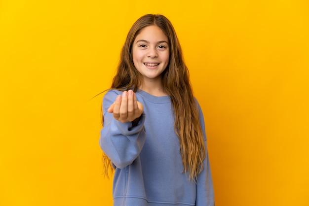Kind over geïsoleerde gele achtergrond die uitnodigt om met de hand te komen. blij dat je gekomen bent
