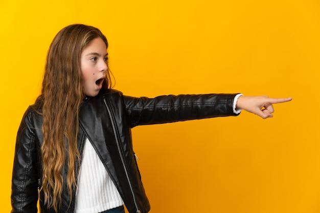 Kind over geïsoleerde gele achtergrond die wegwijst