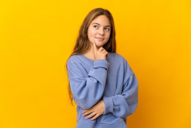 Kind over geïsoleerde gele achtergrond een idee denken terwijl het opzoeken