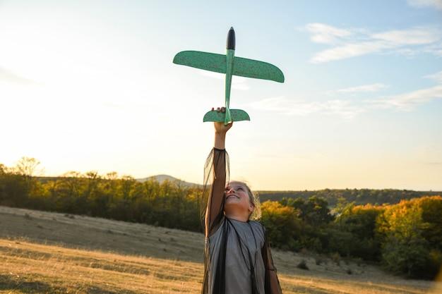 Kind piloot vlieger met vliegtuig dromen van reizen in de zomer