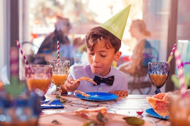 Kind pizza eten op een verjaardagsfeestje