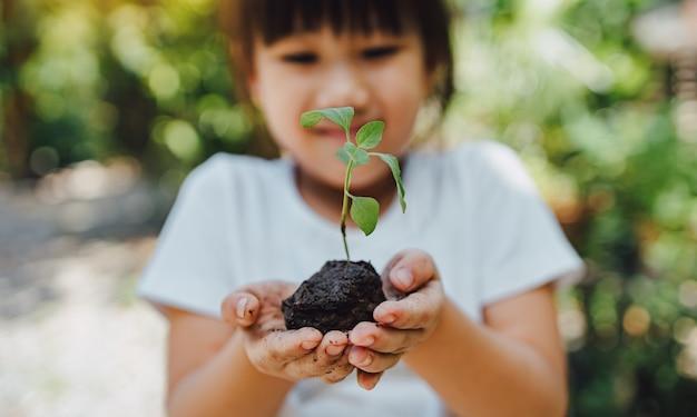 Kind plant een boom om de opwarming van de aarde of klimaatverandering te helpen voorkomen