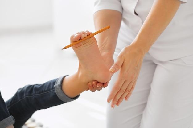 Kind platvoetbehandeling met speciaal massagetapijt. klein meisje op massagemat die oefeningen doet voor platvoetpreventie. voetversterkende oefeningen. podotherapeutische kliniek.