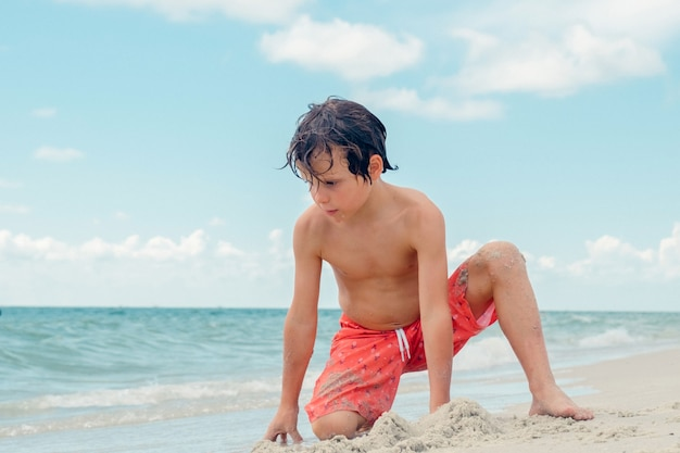 Kind plezier in het zandstrand resort jongen speelt op tropisch strand