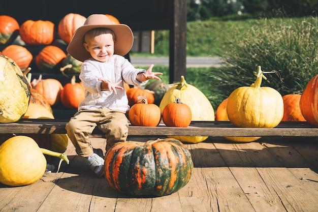 Kind pompoenen plukken op de boerderijmarkt thanksgiving-vakantieseizoen en halloween