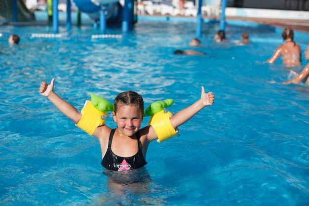 Kind poseert in water gelukkig klein meisje in floaties steekt haar handen op en geniet van haar vakantie op wa...