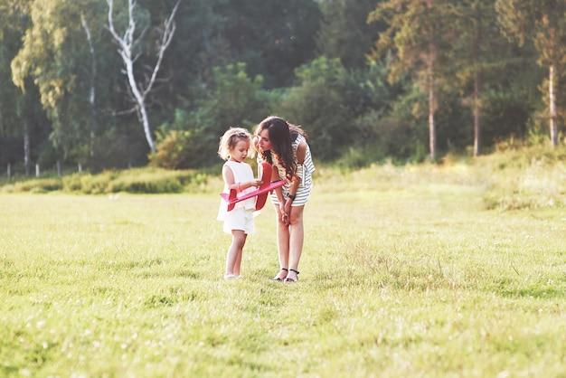 Kind praat over het vliegtuigspeelgoed in haar handen met een moeder buiten